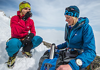 Two female mountaineers as seen drinking a warm tea on a snowy ridge of Aiguilles Marbrées on a cloudy Winter afternnon in Mont Blanc Massif.