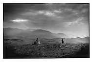 Shepherd boys, backed by the Paghman Range, stay at a safe distance above the Shomali Plain, Afghanistan.
