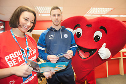 BHF Mascot Hearty and Rebekah Jepson the NHS Stop Smoking advisor, show Sheffield Wednesday footballer Marnick Vermijl some of the literature used to help encourage people to quit smoking at Sheffield City Centre BHF Furniture & Electrical Store during the Stop Smoking Sheffield No smoking Day Campaign<br /> <br /> 2 March 2015<br /> Image © Paul David Drabble <br /> www.pauldaviddrabble.co.uk