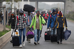 © Licensed to London News Pictures . 24/10/2016 . Calais , France . People leaving the Jungle migrant camp in Calais , Northern France , with their parents , on the day of a planned eviction and start of the destruction of the camp . Photo credit: Joel Goodman/LNP