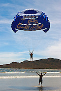 A man is doing parasailing in a beach of Mazatlan.