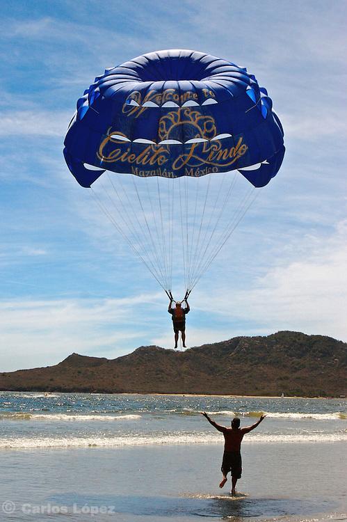 A man is doing parasailing in a beach of Mazatlan.