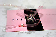 Wedding rings resting on a wedding invitation with pink ribbon strung with pearls
