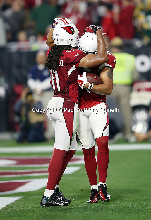 Arizona Cardinals wide receiver Michael Floyd (15) gets a hug from Arizona Cardinals wide receiver Larry Fitzgerald (11) after Floyd catches a fourth quarter tipped pass that gives the Cardinals a 17-13 lead during the NFL NFC Divisional round playoff football game against the Green Bay Packers on Saturday, Jan. 16, 2016 in Glendale, Ariz. The Cardinals won the game in overtime 26-20. (©Paul Anthony Spinelli)