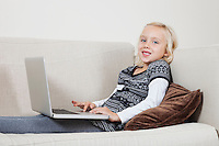 Portrait of happy young girl using laptop on sofa