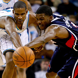 December 26, 2010; New Orleans, LA, USA; New Orleans Hornets small forward Trevor Ariza (1) and Atlanta Hawks shooting guard Joe Johnson (2) scramble for a loose ball during the third quarter at the New Orleans Arena.  The Hornets defeated the Hawks 93-86. Mandatory Credit: Derick E. Hingle