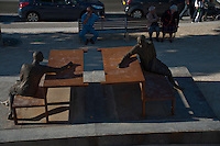 Chartres, France. Public art.  Sculptures of two figures sitting at metal picnic tables in a park.