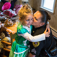 ​Sergeant Crumley embraces her daughter Taylor as Andre waits for her attention.