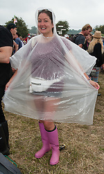 © Licensed to London News Pictures. 26/06/2015. Pilton, UK.  Festival atmosphere at Glastonbury Festival 2015 on Friday Day 3 of the festival. Festival goers in waterproof clothing - yesterday was hot and sunny, while today is overcast with showers.  This years headline acts include Kanye West, The Who and Florence and the Machine, the latter being upgraded in the bill to replace original headline act Foo Fighters.   Photo credit: Richard Isaac/LNP