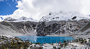 Beautiful turquoise Lake 69 lies under Nevado Chacraraju. As a day trip by car and foot from Huaraz, hike to Lake 69 (4600 meters elevation, 8 miles or 13k round trip with 800 meters gain) in the Cordillera Blanca, Andes Mountains, Peru, South America. This panorama was stitched from 6 overlapping photos.