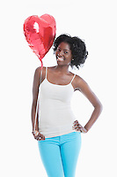 Portrait of happy young woman with heart shaped balloon standing over white background
