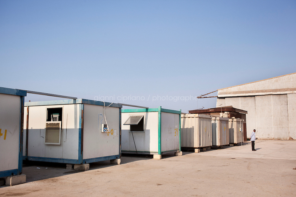 Hal Far, Malta - 20 August, 2012:  A migrant stands outside the container he lives in at the Hangar Open Centre, in Hal Far, Malta, on 20 August, 2012. <br /> <br /> The Hangar Open Center is a field with an ex-aircraft hangar which, until 2011, included Swiss Red Cross tents in a dark, non lit space in very poor conditions and with inflamable oil on the floor. Today, the hangar is closed and the migrants live in 34 external containers with no water. <br /> <br /> The Open Centres in Malta serve as a temporary accomodation facility, but they ended becoming permanent accomodation centres, except for those immigrants who receive subsidiary protection or refugee status and that are sent to countries such as the United States, Germany, Poland, and others. All immigrants who enter in Malta illegally are detained. Upon arrival to Malta, irregular migrants and asylum seekers are sent to one of three dedicated immigration detention facilities. Once apprehended by the authorities, immigrants remain in detention even after they apply for refugee status. detention lasts as long as it takes for asylum claims to be determined. This usually takes months; asylum seekers often wait five to 10 months for their first interview with the Refugee Commissioner. Asylum seekers may be detained for up to 12 months: at this point, if their claim is still pending, they are released and transferred to an Open Center.<br /> <br /> Gianni Cipriano for The New York Times