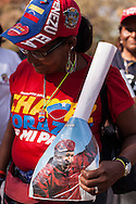 Chavista woman during the funeral of Hugo Chávez, Caracas, 8th March 2013. During Hugo Chávez funeral many people and stand sold miscellaneous articles that perpetuate Chávez presence. Everything from T-shirts, badges, earrings, baseball caps, sun glasses seemed suitable to have the President's image. The cult of Chávez is now more alive than ever.
