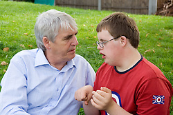 Father talking to teenage son with Down's Syndrome,