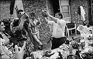 ROMANIAN ORTHODOX EASTER CELEBRATIONS. A TABLE OF FOOD, DRINK AND GIFTS IS CARRIED TO A  CHILDS' GODFATHERS HOUSE. IN THIS PHOTO PUIA AND LENA MIHAI BREAK BREAD TOGETHER. SINTESTI, ROMANIA, EASTER 1995..©JEREMY SUTTON-HIBBERT 2000..TEL./FAX. +44-141-649-2912..TEL. +44-7831-138817.