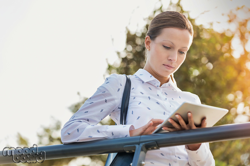 Portrait of young attractive businesswoman using digital tablet while leaning on railing
