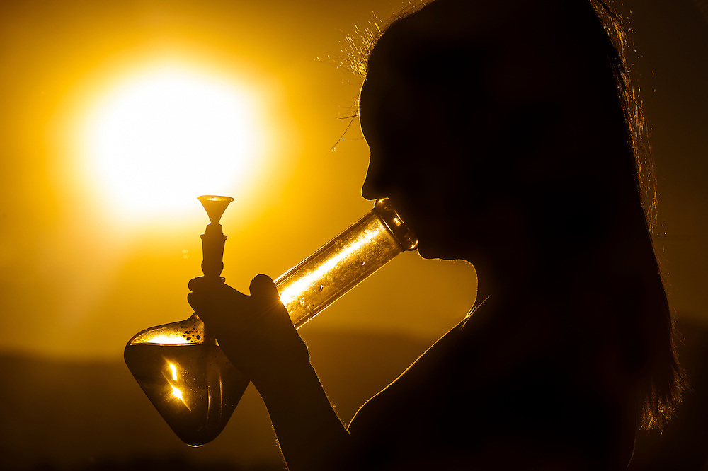 A young woman smoking marijuana in a bong, Littleton, Colorado USA. Colorado was the first state to legalize the sale of marijuana for recreational use in 2014.