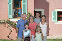 Portrait of three-generation family with two children (6-9) in front of house