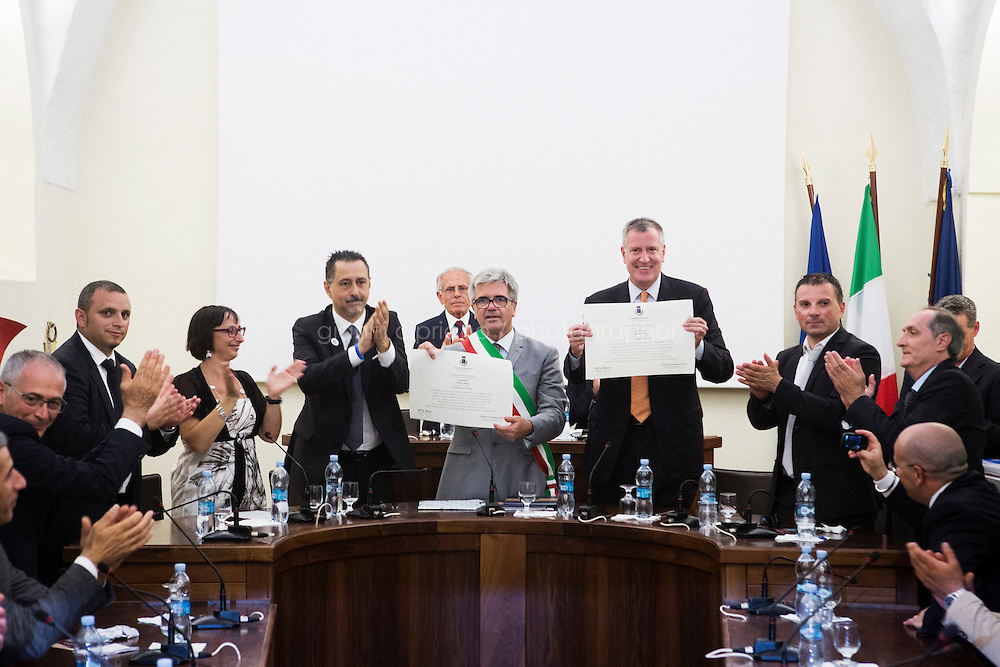 GRASSANO, ITALY - 24 JULY 2014: Mayor of New York Bill de Blasio and Mayor of Grassano Francesco Sanseverino (on the left of de Blasio) pose for a picture during the ceremony of  conferment of the   honorary citizenship to Mr de Blasio at the city council room in Grassano, his ancestral home town in Italy, on July 24th 2014.<br /> <br /> New York City Mayor Bill de Blasio arrived in Italy with his family Sunday morning for an 8-day summer vacation that includes meetings with government officials and sightseeing in his ancestral homeland.