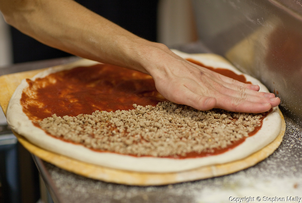 Aaron Schilling spreads toppings on a pizza as he works at Saint Giuseppe's Heavenly Pizza in Moline, Illinois on Tuesday November 9, 2010. The pizza shop is owned by Congressman-elect Robert Schilling (IL-17).