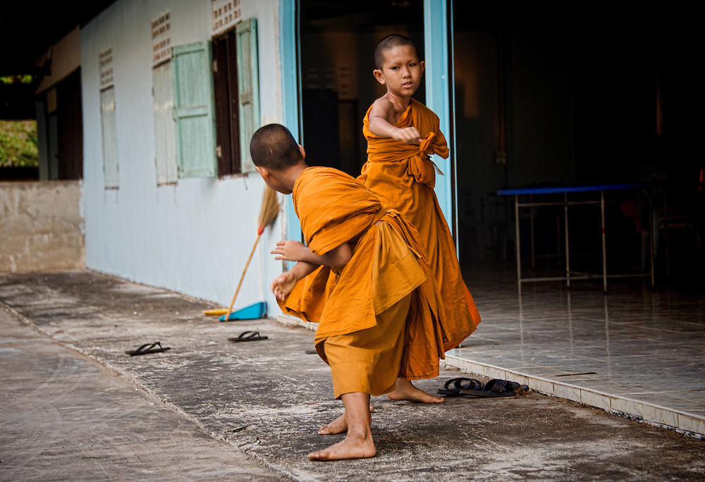 Young monks engage in horseplay in Rural Nakhon Nayok, Thailand.