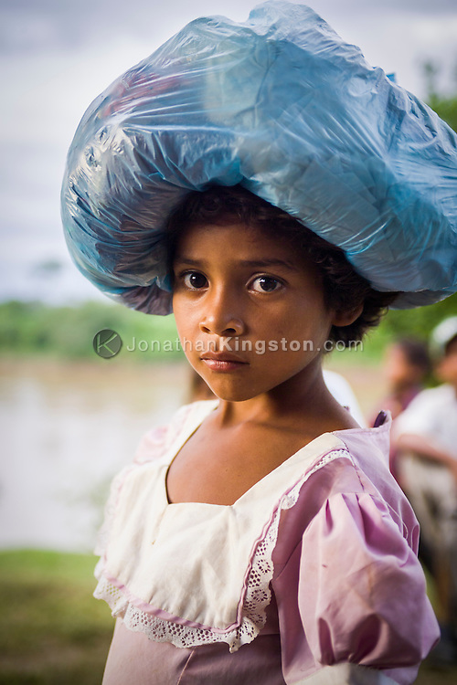 A young Miskito girl carries a sack of goods on her head in Krin Krin, Nicaragua.