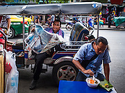 12 JANUARY 2017 - BANGKOK, THAILAND:         A tuk-tuk driver reads a newspaper while waiting for a fare in Bo Bae market. Bo Bae Market is a sprawling wholesale clothing market in Bangkok. There are reportedly more than 1,200 stalls selling clothes made in Thailand and neighboring countries. Bangkok officials have threatened to shut down parts of Bo Bae market, but so far it has escaped the fate of the other street markets that have been shut down.     PHOTO BY JACK KURTZ