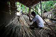 As his mother weaves bamboo mats on the other side of the wall, Nguyen Van Doan, 16, assists her by preparing the long strands of bamboo. In their cooperation with local NGO Anh Duong, and is international partner Vietnam Plus, the family are able to procure the materials for production and sale of the mats, which has help them raise their annual income significantly.