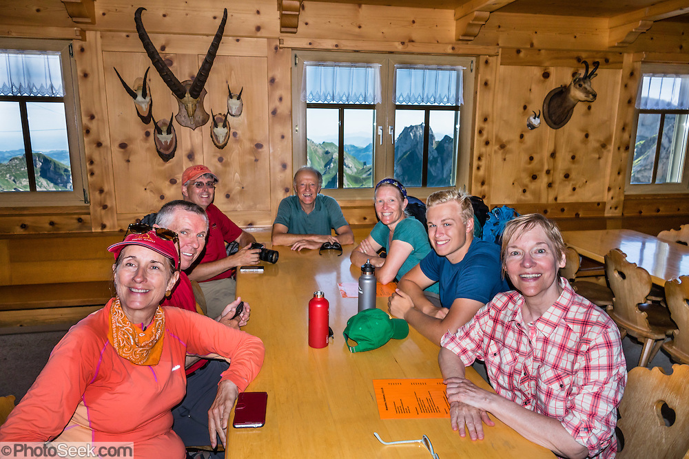 Smiling hikers order lunch in the wood dining room of Berggasthaus Rotsteinpass (2120 m) in the Alpstein limestone mountain range, Appenzell Alps, Switzerland, Europe. Appenzell Innerrhoden is Switzerland's most traditional and smallest-population canton (second smallest by area). For licensing options, please inquire.