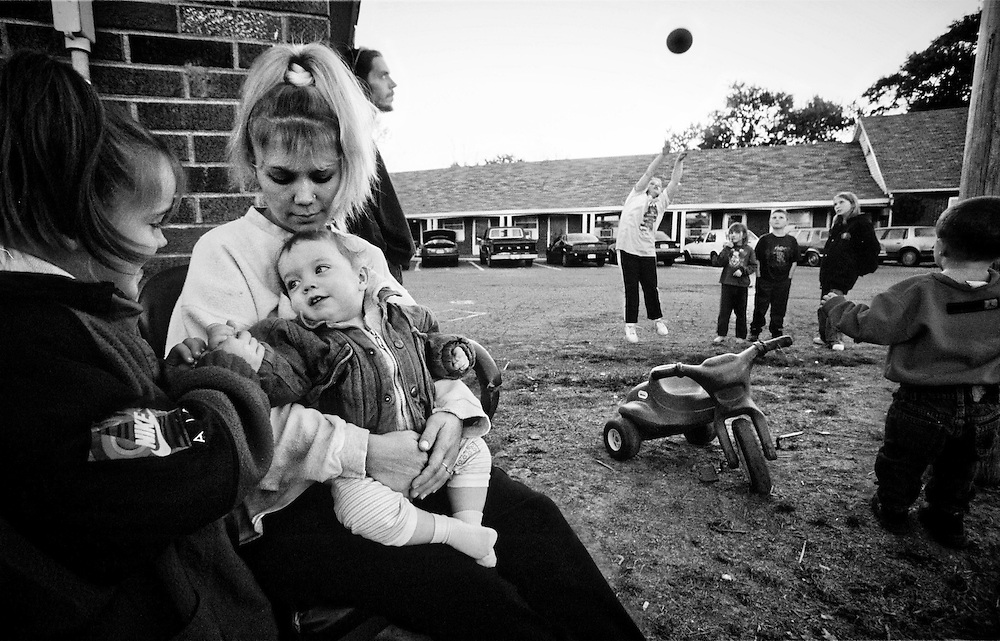 Cora McNeil, center, holds her youngest son, Christian, 1, while her daughter Morgan, 6, entertains him outside their home at the Town and Country Motel west of Greenfield Ind. The rest of the family plays basketball with neighbors in the parking lot of the old motel. McNeil, her fiance, and their six children live in two rooms at the motel. More than a dozen children call the motel home. (Mike Fender Photo) w/ story