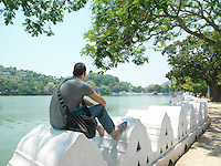Young man sitting on surrounding wall by river back view