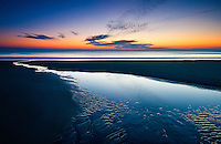 a receding tidal pool iluminates the beach and leads the eye out into the ocean and coming sunrise in the pre-dawn light of the Outer Banks