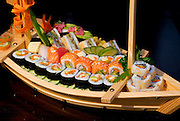 Assortment of Sushi on a wooden boat shaped platter including: Sushi Maki, futo maki, Insideout and sushi sandwich