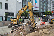 An excavator operator sifts large material from soil as a full dump truck exits the site.