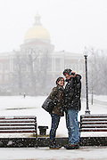Meggie Foley and Lucian Marts, who are recent transplants to Brookline, Massachusetts, via Atlanta, Georgia, snap a photo of themselves in front of the Massachusetts State House as Winter Storm Nemo begins to drop snow in Boston, Massachusetts, U.S., on Friday, Feb. 8, 2013. The storm is expected to dump upwards of 2 feet of snow on the region overnight. Photographer: Kelvin Ma/Bloomberg