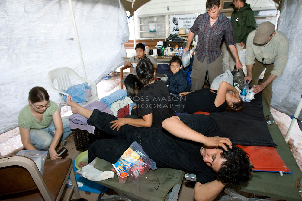 Migrant Francisco writhes in pain as No More Deaths volunteer Heidi Kennedy -a nurse-(left) cleans his blistered foot with Hydrogen Peroxide prior to bandaging at the camp in southern Arizona.