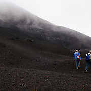 A guide and hiker at the summit of Pacaya Volcano. Pacaya is an active volcano that forms part of the Central America Volcanic Arc. It forms a popular tourist destination easily accessible from Antigua and Guatemala City. Situated within the Pacaya National Park, it rises to 2,552 metres (8,373 ft). Its last major eruption, which caused considerable damange to nearby villages and reshaped the summit, was in May 2010. That eruption and scattered volcanic ash over much of the nearby area, prompting school closings and emergency evacuations and cleared much of the vegetation near the top of the mountain.