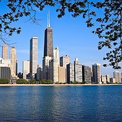 Chicago skyline. Chicago skyscrapers with the John Hancock Center building. Scene is located in the Northern Streeterville area of Chicago. In the foreground is Lake Michigan with tree branches and leaves. Available as a high resolution print or stock photo.