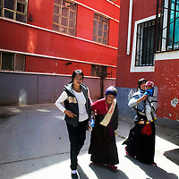 TONGREN, APRIL 4, 2012 : Tibetan women  walk past  a settlement for nomads created by the local government.