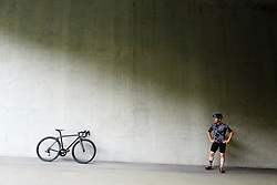 Male Cyclist with Bicycle standing by Concrete Wall