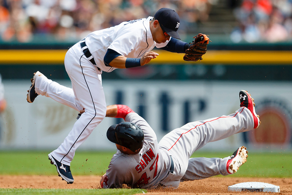 Aug 9, 2015; Detroit, MI, USA; Detroit Tigers shortstop Jose Iglesias (1) leaps over Boston Red Sox first baseman Travis Shaw (47) as he slides into second base in the second inning at Comerica Park. Mandatory Credit: Rick Osentoski-USA TODAY Sports