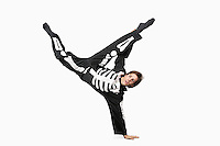 Young man in skeleton costume break dancing against white background