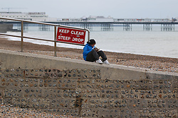 © Licensed to London News Pictures. 20/11/2014. Brighton, UK. A woman reading a book on the beach. A cold and dry day on Brighton Beach with temperatures expected to reach 11C down the South Coast. Photo credit : Hugo Michiels/LNP
