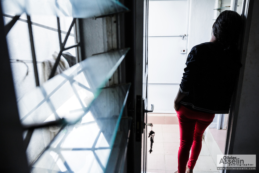 """Rebecca, 21, stands in the doorway of a friend's apartment in Abidjan, Cote d'Ivoire on Wednesday July 17, 2013. Rebecca exchanged sex for money for about six weeks until she decided to stop. """"I couldn't have a clean conscience anymore"""", she says. She had started working as a sex worker after her father refused to pay for her school fees, forcing her to drop out. She's investing the money she made into a boutique she says will help her go back to school."""