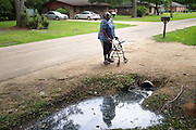 "HAYNEVILLE, AL – MAY 21, 2015: Charlie Mae Martin Holcombe, 66, moved to her current home in Hayneville in 1984, where the sewage from a lagoon across the street regularly backs up into her front yard. ""This whole area floods, all over the yard,"" she said. ""You can count the few times that this ditch is dry."" Inadequate sewage treatment has plagued Alabama's poor Black Belt community for decades, often leading to problems of overflow and contamination of the area's water supply."