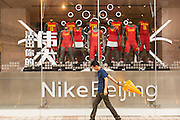 Shopper walks past the Nike shop along Wangfujing Street shopping district on a rainy day in Beijing, China