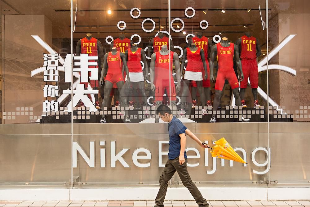 Shopper walks past the Nike shop along Wangfujing Street shopping district on a rainy day in Beijing, China