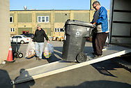 A man stands on a ramp with a garbage can while another man in the background carries bags in the parking lot of Worth A Second Look, a second hand store that is part of The Working Centre in Kitchener, Ontario, Canada. Both men are part of Job Cafe, an informal casual work program of The Working Centre.