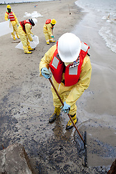 Relief worker cleaning oil from the texas city beach