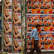 Man walking by billboard advertisments near Taksim Square, in Istanbul, Turkey.